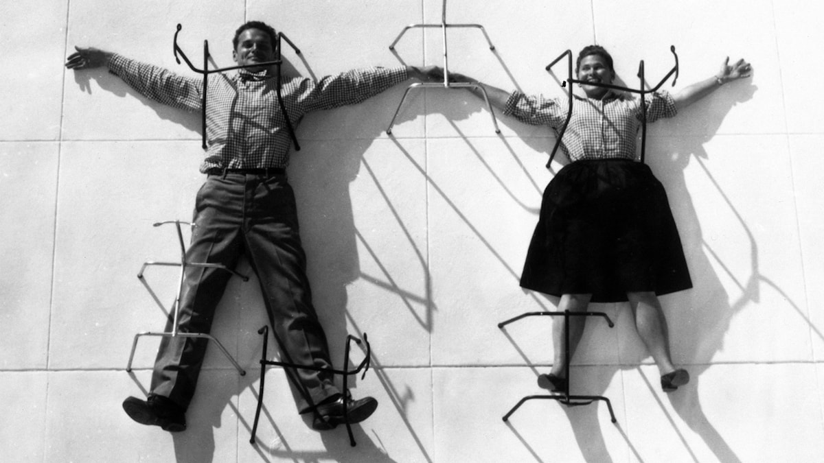 3-The-World-of-Charles-and-Ray-Eames-Charles-and-Ray-Eames-posing-with-chair-bases-©-Eames-Office-LLC