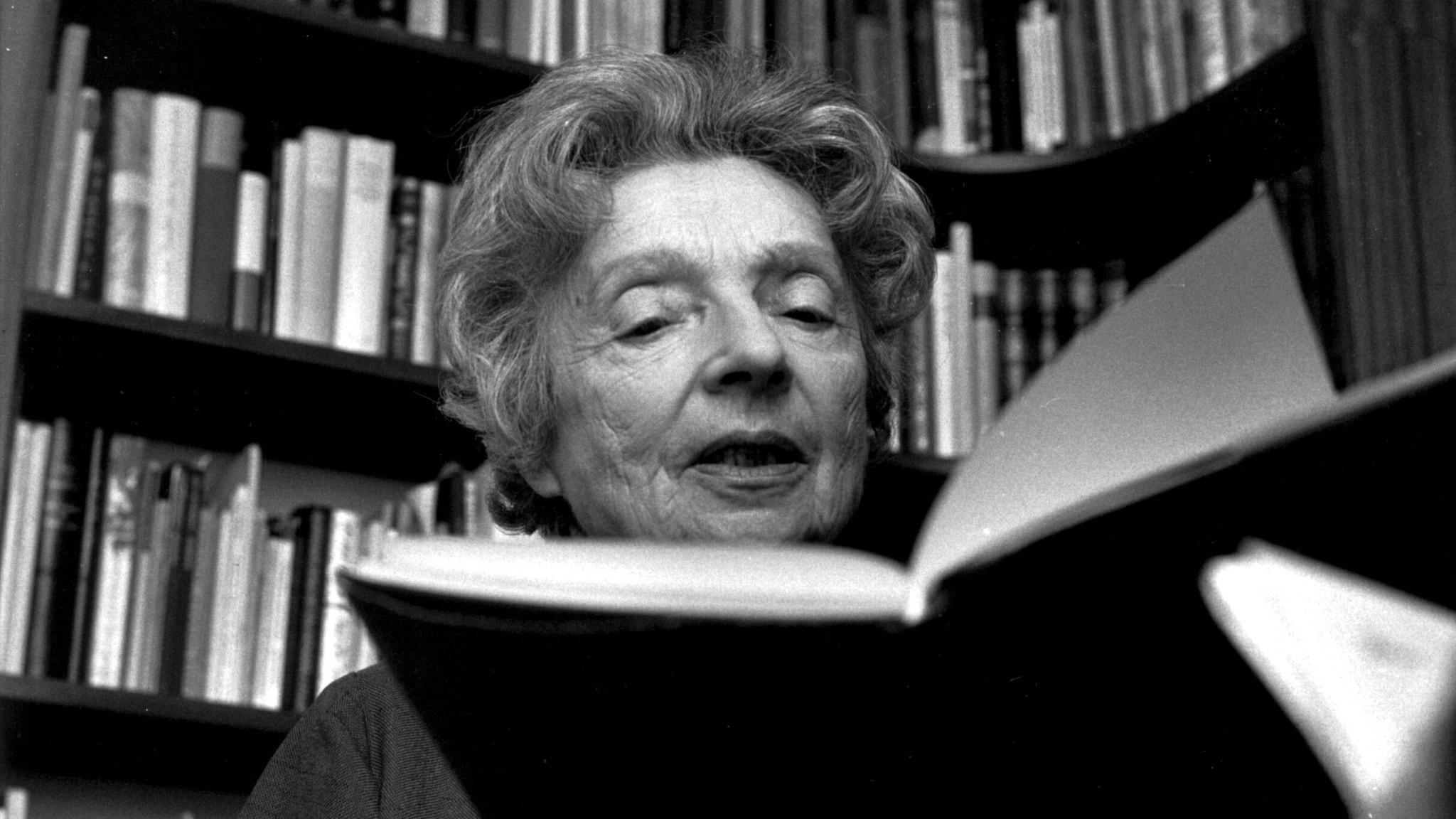 äldre kvinna med uppslagen bok
