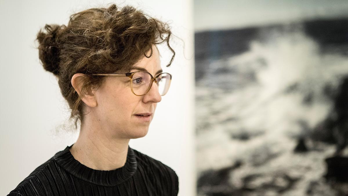 Konstnären Gunnel Wåhlstrand framför en av hennes detaljerade målningar.