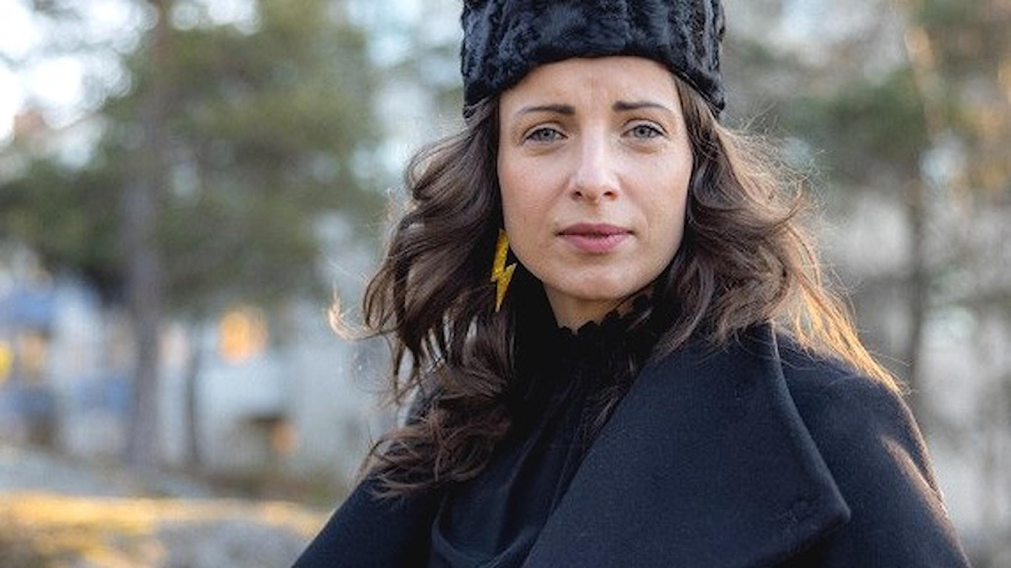 Kvinna i pälsmössa och kappa utomhus