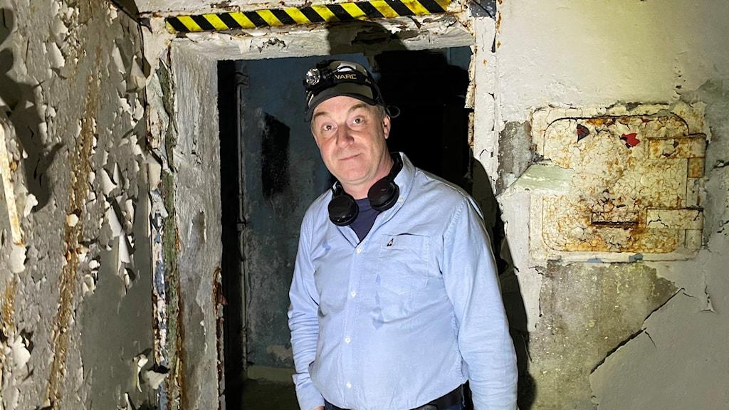 en man i skjorta och keps inne i en grotta med rum