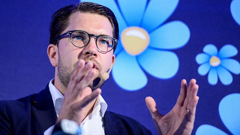 Mörkhårig man med glasögon gestikulerar med händerna framför bakgrund med ljusblå blommor på mörkblå grund