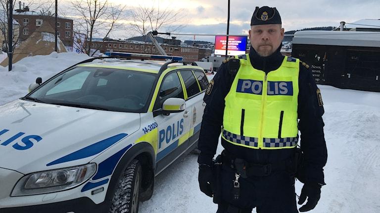 Polis och polisbil på stortorget i Östersund.
