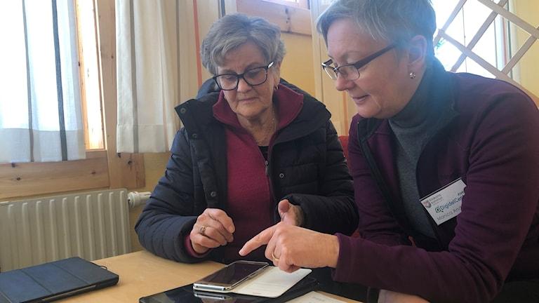 Två kvinnor mobilsurfar