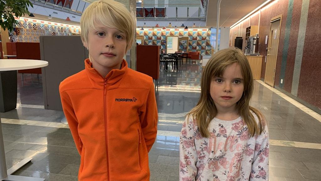 Två barn, en pojke i orange tröja, en flicka i blommig tröja