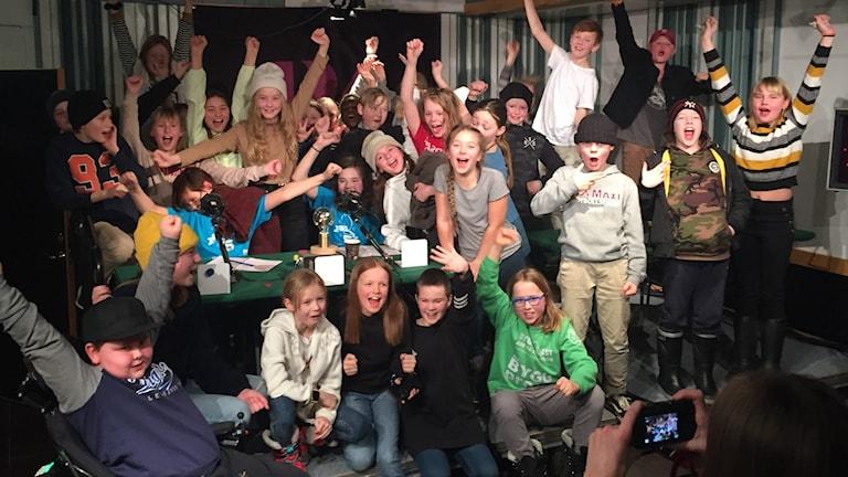 Glad skolklass sträcker upp händerna i taket