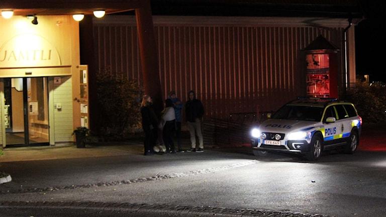 Ungdomar och en polisbil utanför Jamtli i Östersund nattetid.