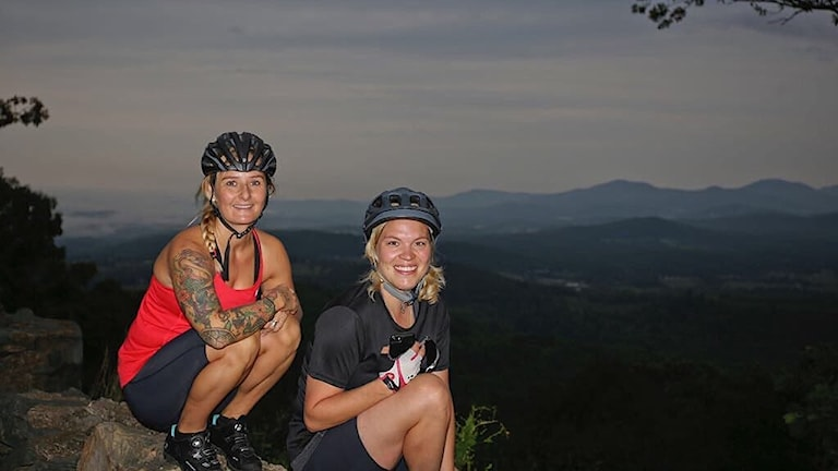 Två kvinnor i cykelhjälm framför en bergskedja.