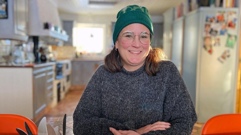 En leende kvinna med toppluva och glasögon som sitter i ett kök