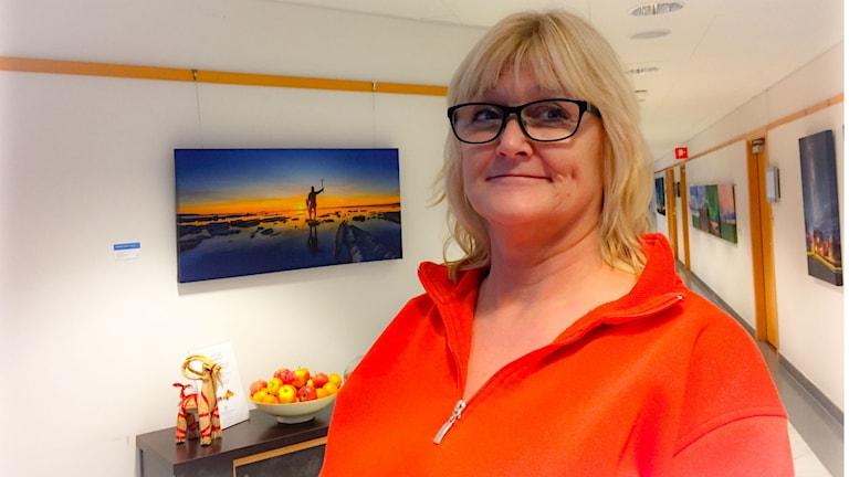 Kvinna i orange tröja står i hotellkorridor.