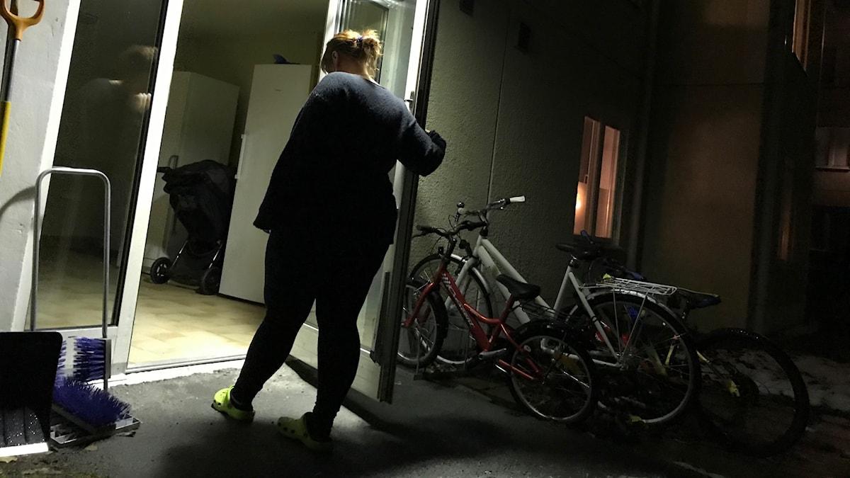 Kvinna står i dörröppning, man ser inte hennes ansikte