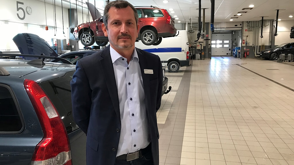 Man i kostym står framför ett antal bilar inne i en stilren bilverkstad. En bil ser ut att sväv bakom honom, men ger intrycket av att vara upplyft av en anordning av något slag.