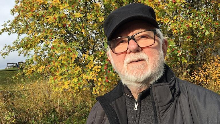 Äldre man med glasögon och vitt skägg.