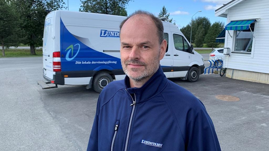 En man i blåjacka som står på en parkering.