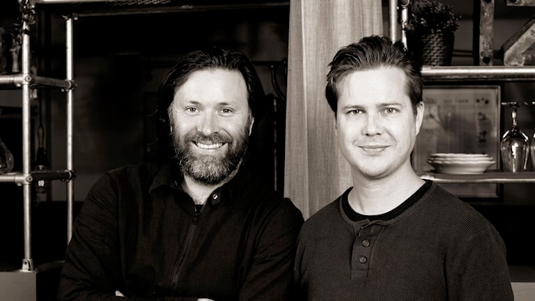 Två manliga författare står framför hylla