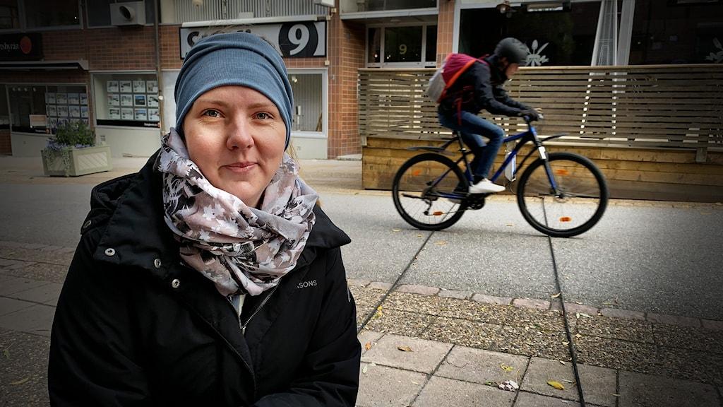 Kvinna framför cykelväg med mätslangar spända över vägen för att mäta antalet cyklar.