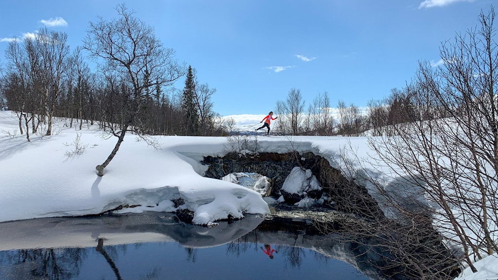 en längdskidåkare i strålande solsken på fjället med spegelbilden i en bäck