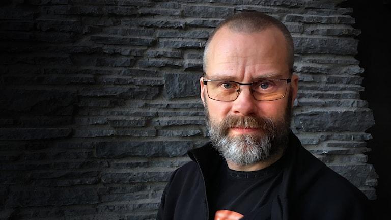 Stefan Edfeldt, en man i skägg och glasögon som står mot stenvägg.