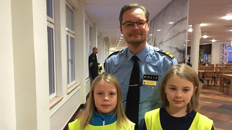 En lång man i polisuniform med glasögon och skägg, framför står två små flickor med blont hår och gula varselvästar som det står skolpolis på. Alla ler och tittar rakt in i kameran.