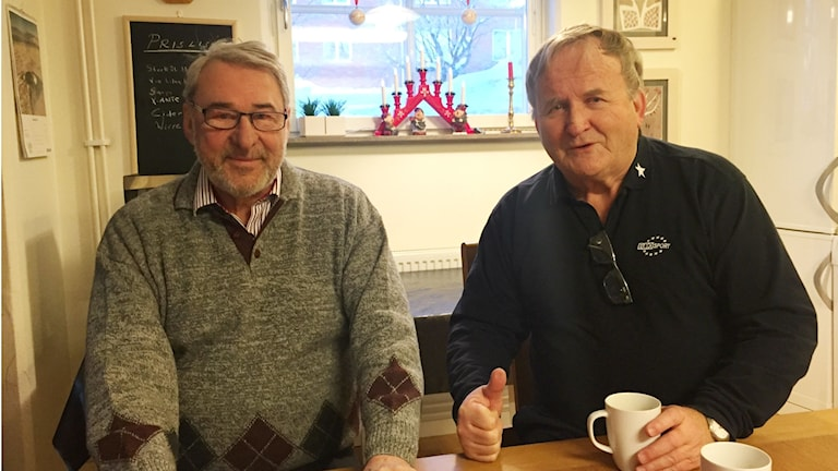 Två män som sitter vid ett bord.