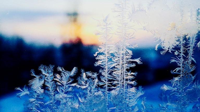 Iskristaller på fönster med blått landskap bakom