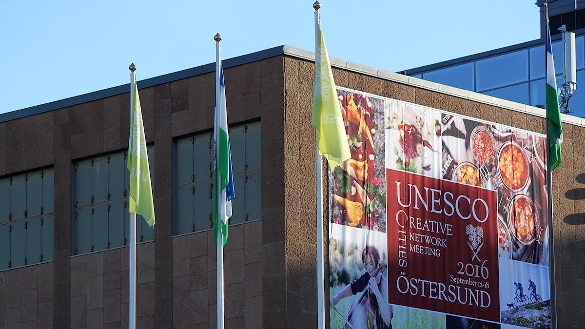 Stor tygskylt på fasad med matbilder som reklam för evenemang kring mat