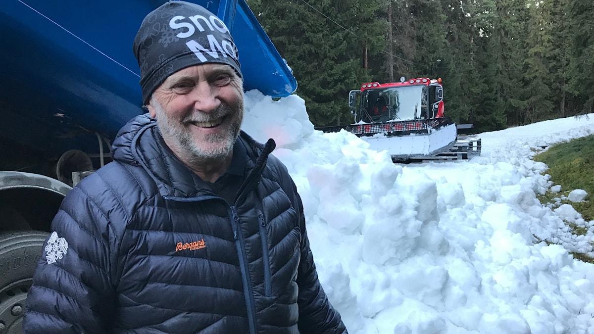 En man i svart mössa och jacka står framför bakdelen av en lastbil som tippar snö på marken i skogen. I bakgrunden syns en röd pistmaskin.