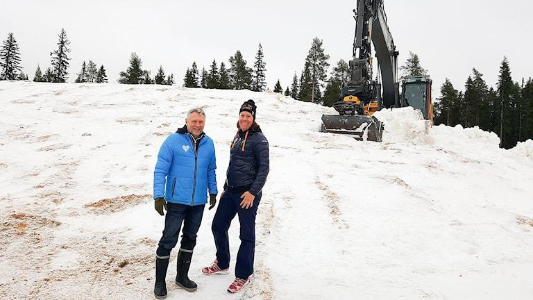 En medelålders man och en yngre kvinna poserar framför en gigantisk snöhög. Bakom skymtar en grävmaskin.