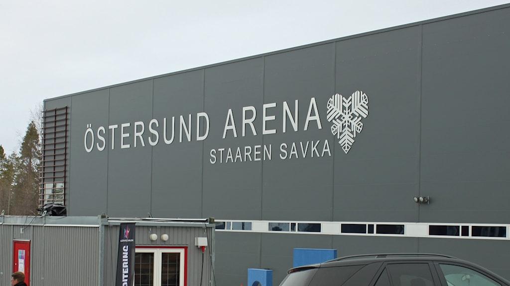 Bild på en grå vägg till Östersund Arena där den stora skylten med namnet hänger.
