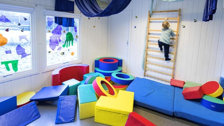 Barn som leker i färgglatt förskolerum, klättrar på ribbstol