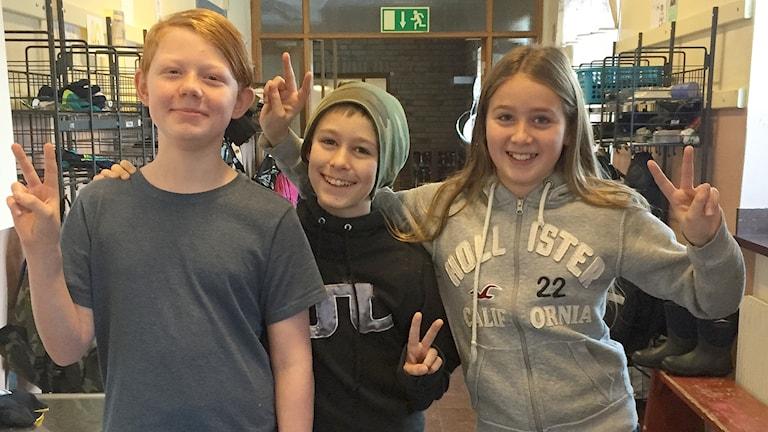 Tre elever i femte klass står i skolkorridor och gör segertecken