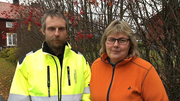 Man i reflexjacka och kvinna i fleecejacka står framför rönnbärsbuske.