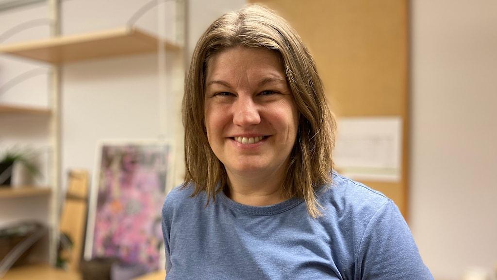 Leende kvinna med mellanlångt, askblont hår och blå kortärmad tröja i kontorslokal