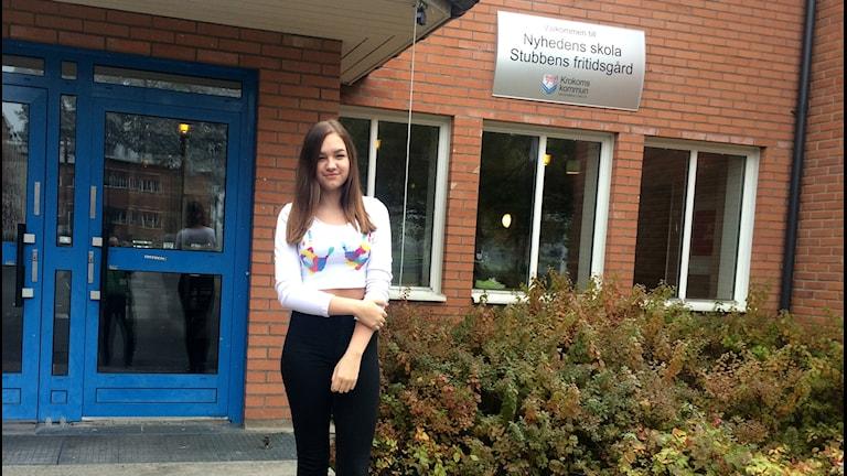 Kvinnlig eleve framför skola.