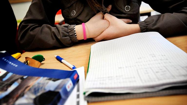 Skolelev med block och penna framför sig.