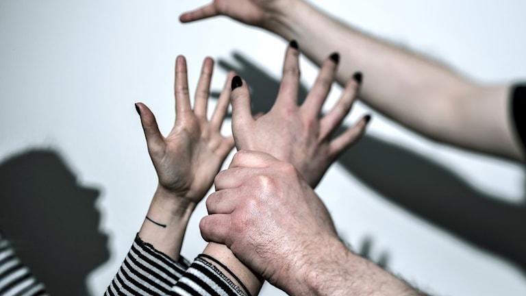 Bild som visar fyra händer, man greppar kvinna,  kvinnomisshandel