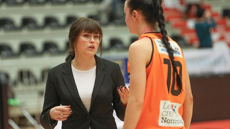 Kvinna i kavaj och basketspelare i orangea kläder