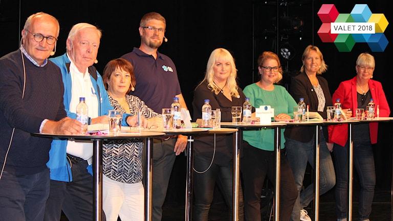 Åtta personer, män och kvinnor, står uppradade vid ståbord vid debatt
