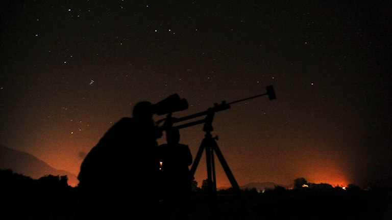 People look through telescopes to get a closer view of a spectacular meteor shower in the town of Ano Vrontou, northern Greece, Sunday 10 Aug. 2008. The phenomenon, known as the Perseid meteor shower, occurs at mid-August and  is caused by falling debris from the Swift-Tuttle comet. (AP Photo/Nikolas Giakoumidis)