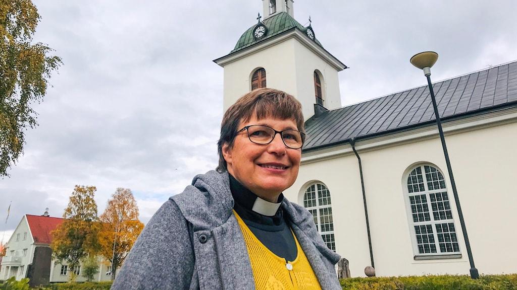 En kyrkoherde med grå kappa och gul tröja som står framför en kyrka i höstiga färger.