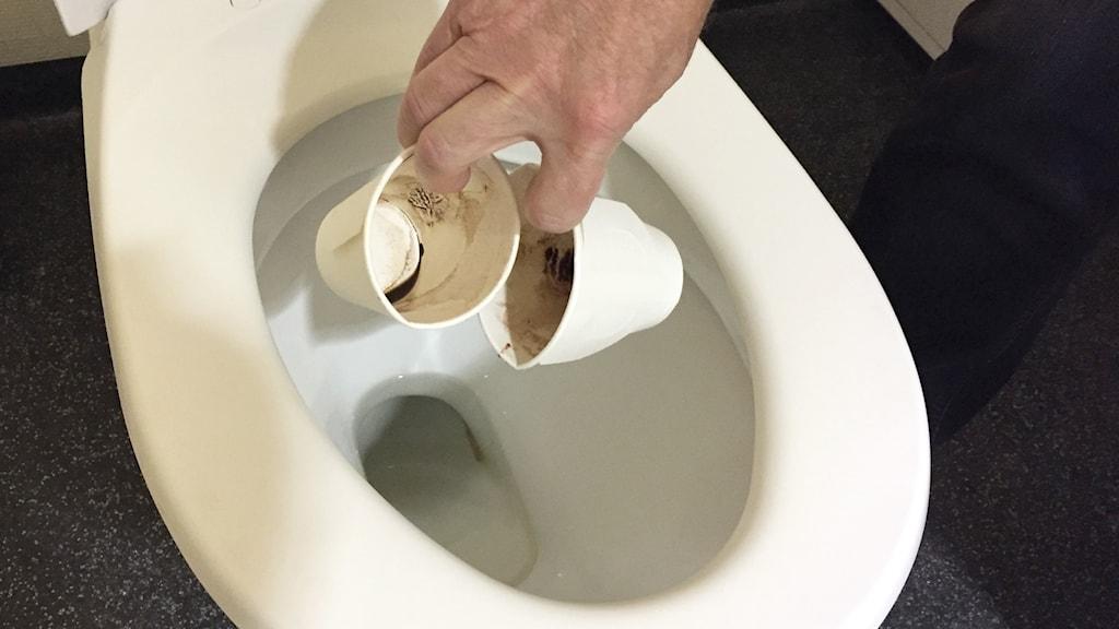 Två pappersmuggar som akstas i toaletten