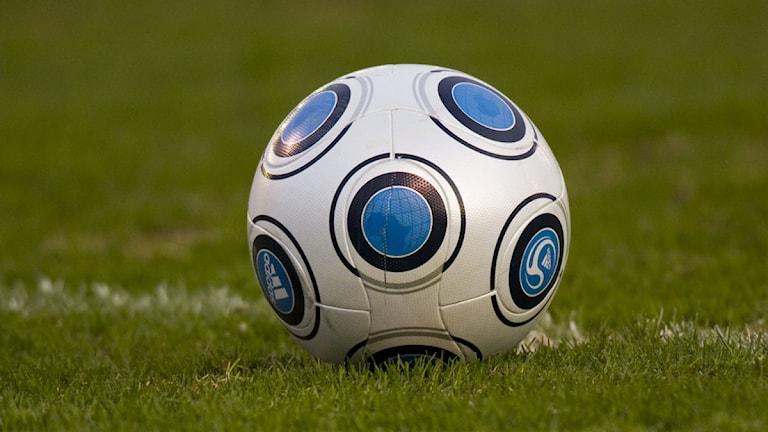 En fotboll på grön en gräsplan.