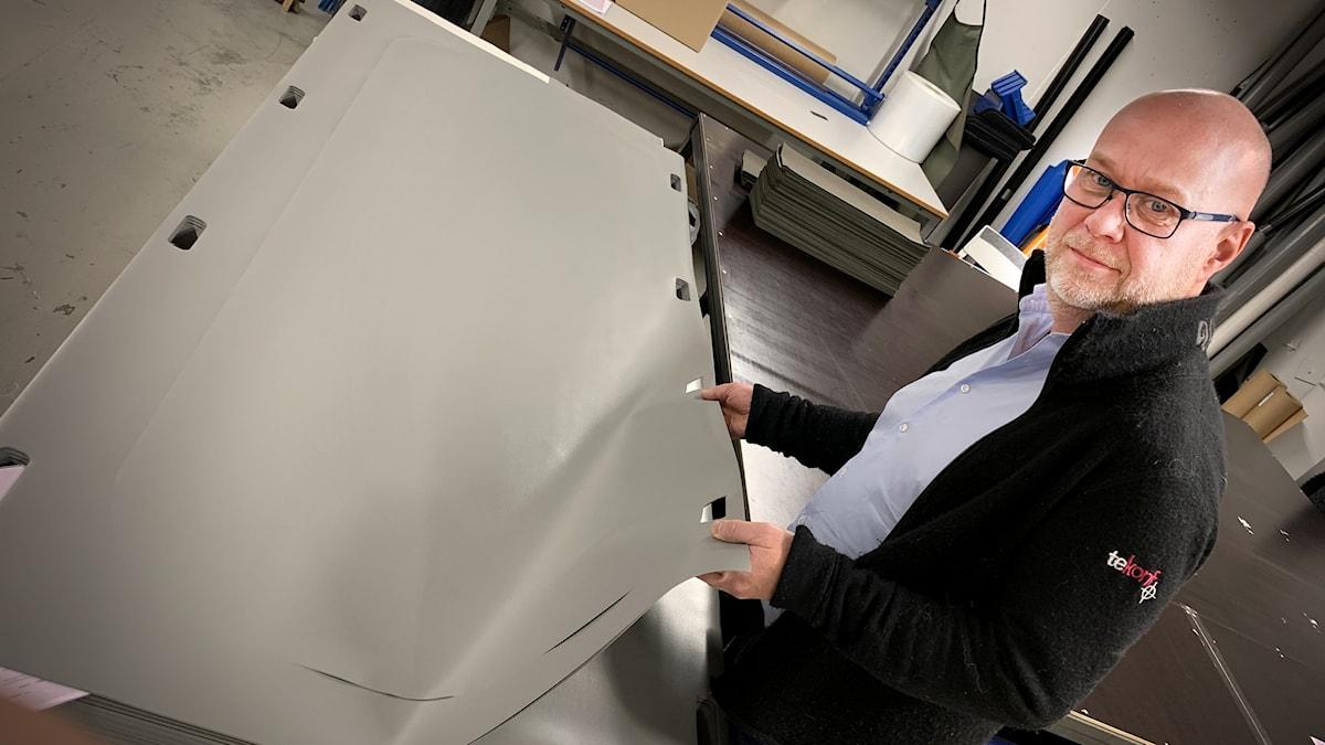 Man visar upp materialet av plastväv som ska sys ihop liksäckar.