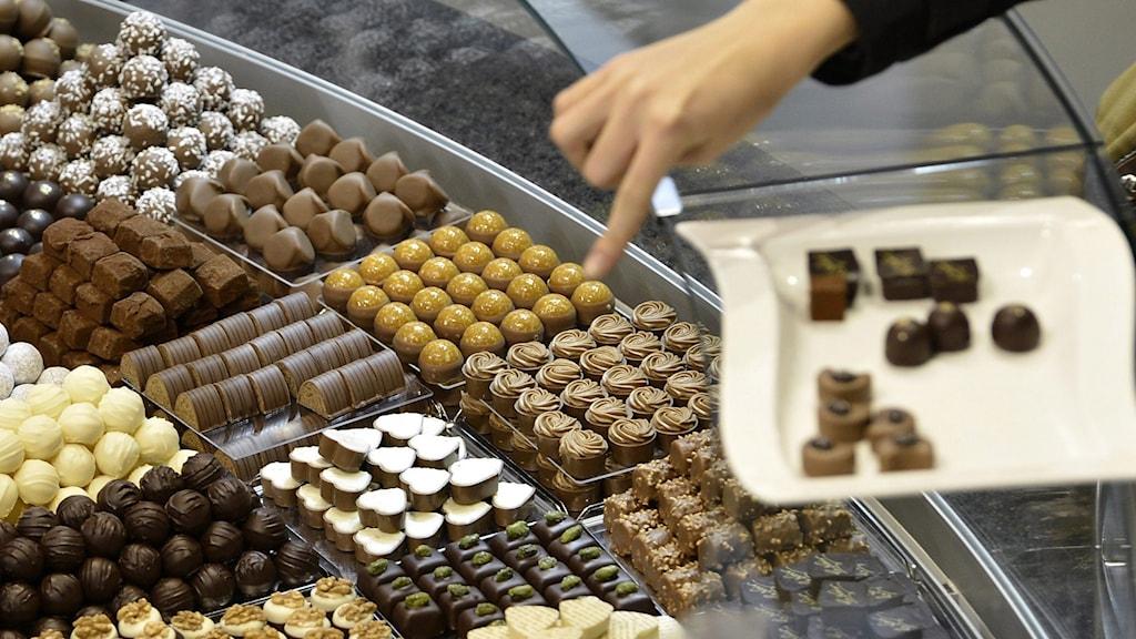 Person pekar på en mäng chokladbitar upplagda på fat