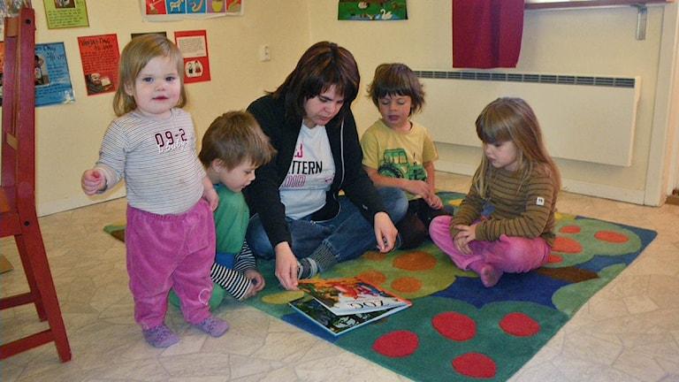 Tre barn och en lärare läser sitter på golvet