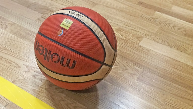 En orange basketboll ligger på golv i sporthall