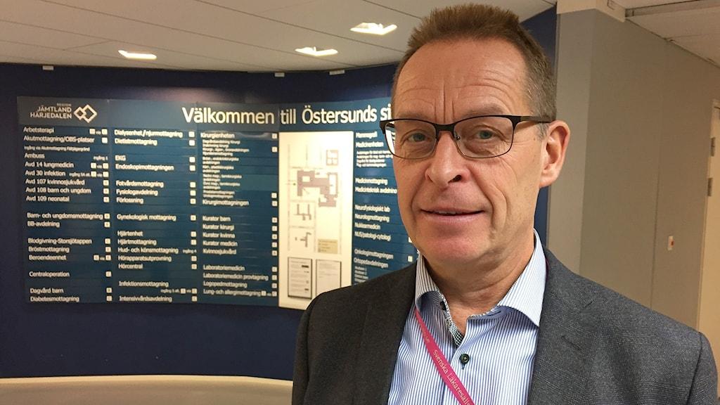 Man med glasögon vid skylt med avdelningar på Östersunds sjukhus