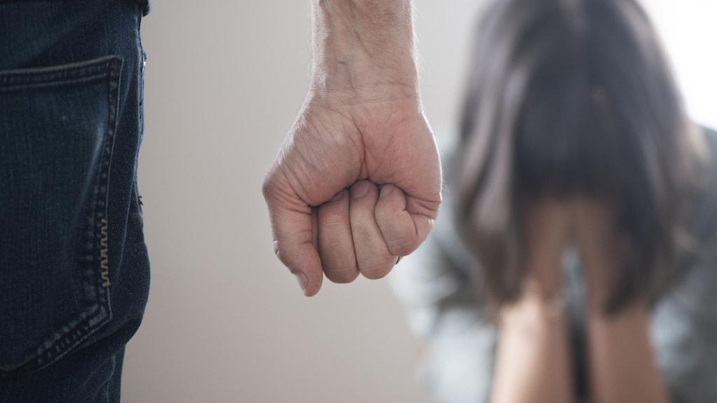 En man med knuten hand och en kvinna som håller för ansiktet