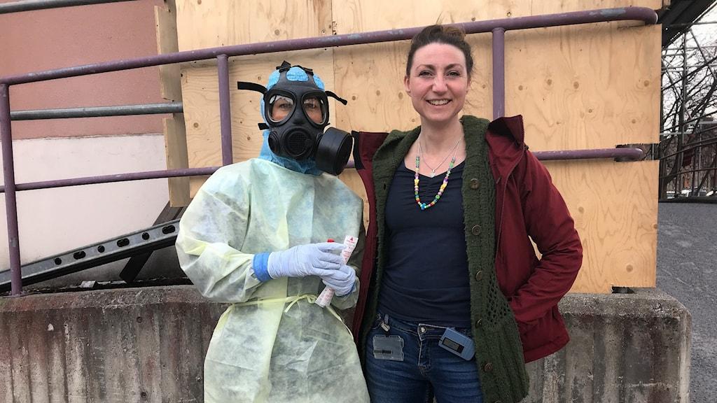 Kvinna i skyddsutrustning med andningsmask står tillsammans med en annan kvinna i röd jacka utanför Östersunds sjukhus.