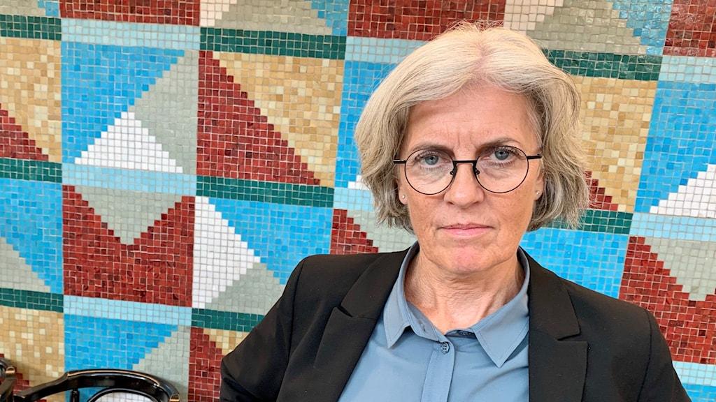 En kvinna i grått hår och glasögon står mot en mosaikvägg.